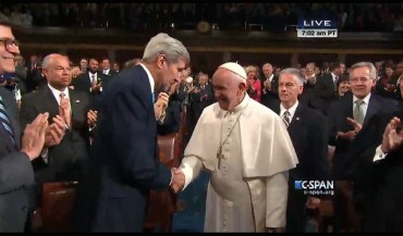 Pope Francis shakes hands with Secretary of State John Kerry as he enters the House chamber to address a joint session of Congress.